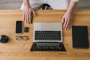 E-biznes: Pan siedzi przed laptopem, na biurku leżą okulary, telefon, notesik oraz karta płatnicza
