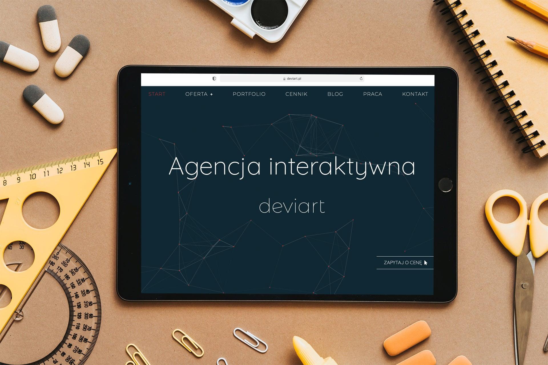 Strona internetowa otworzona na tablecie. Tablet leży na biurku. wokół tabletu leżą nożyczki, linijka, notesik, długopis.