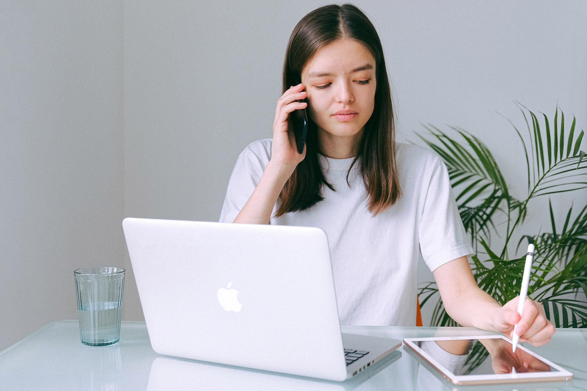Komunikacja: Pani prowadzi rozmowę przez telefon, notuje uwagi klienta na tablecie, ma przed sobą również laptop. Na stole stoi również szklanka z wodą.