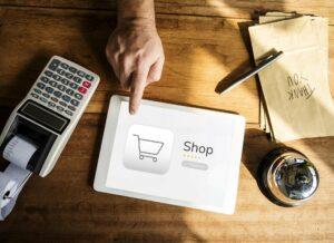 sklep internetowy: na biurku leży laptop z ikonką sklepu internetowego, kasa fiskalna, długopis i kartka na której napis